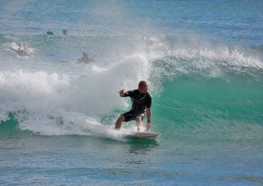 ざばっと波にのるサーファー