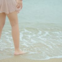 ぴちゃぴちゃと波を受ける女性