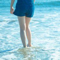 ばしゃばしゃと波打ち際を歩く女性