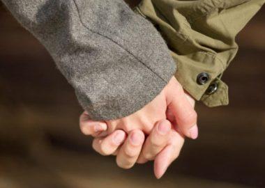 ぎゅっと手を握るカップル