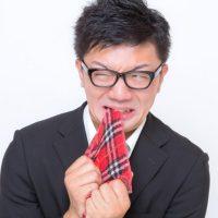 ハンカチをぎりりと噛む男性