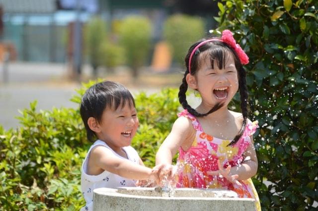 あはあはと楽しげに水遊びをする子ども