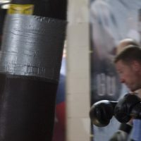 がっつんとサンドバッグを叩くボクサー