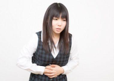 胃がきりきりと痛む女性