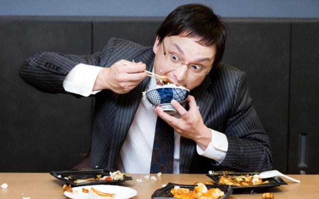 がっつりと昼食を食べる男性