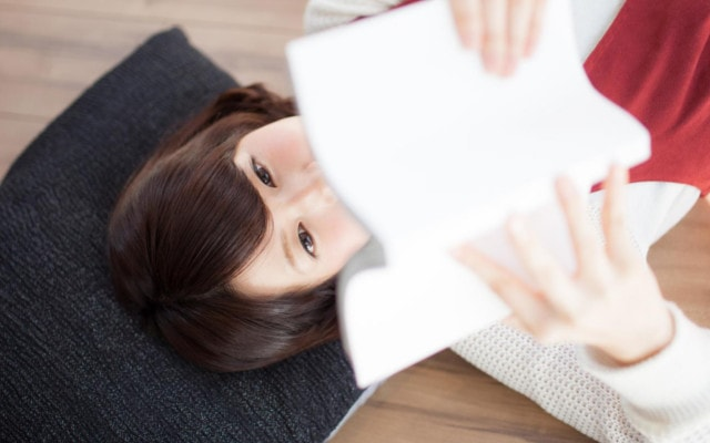 本を読みくすりくすりと笑う女性