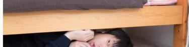 そーっとベッドの下に隠れる男性