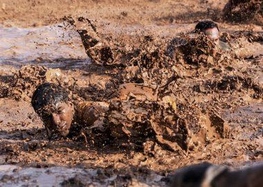 ずぼんと泥に浸かる男性