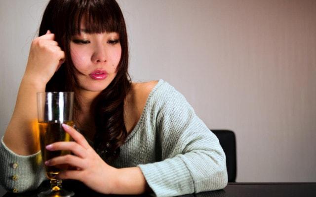 ぐでんとお酒に酔う女性