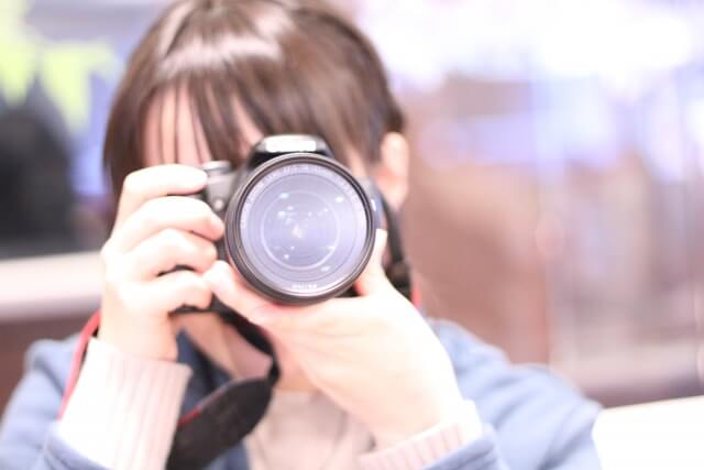 ぱしゃぱしゃとカメラのシャッターを切る女性