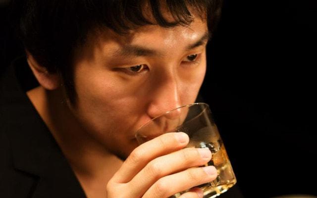 ウィスキーをぐびりちびりと飲む男性