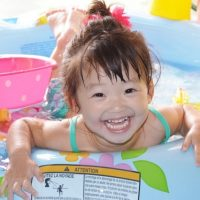 じゃぶじゃぶとプールで遊ぶ女の子