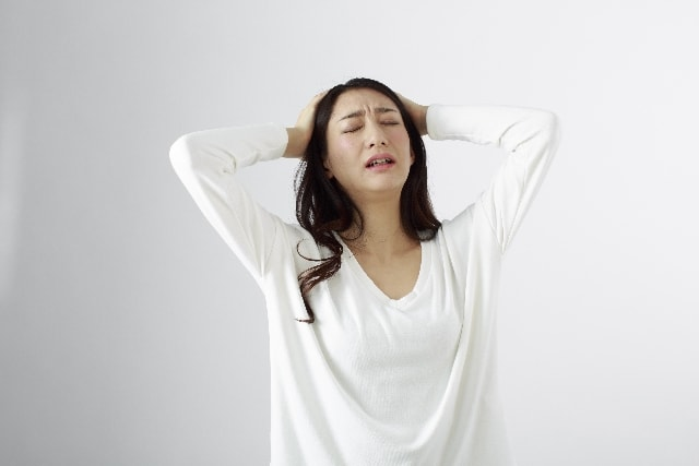がびーんと頭を抱える女性