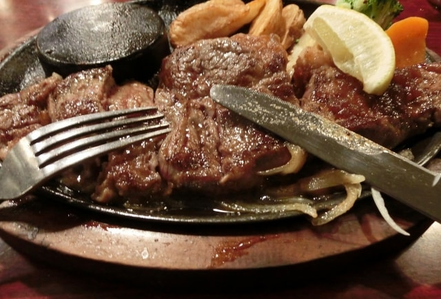 じゅーじゅーと音をたてるステーキ