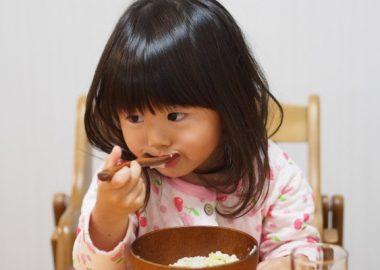 じゅるっとおかゆを食べる女の子