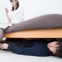 そろりそろりとベッドの下に隠れる男性