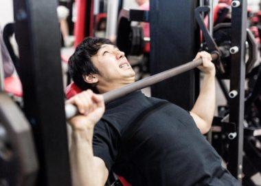 ぐっぐっと力を込めてバーベルを上げる男性