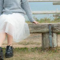 きしきしと音がなるベンチに座る女性